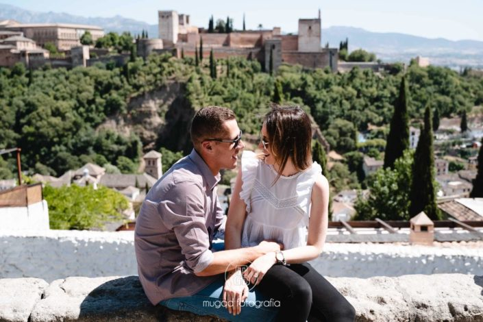 Pareja sentada Alhambra de fondo